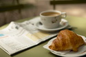 Close up of croissant with coffee and a newspaper